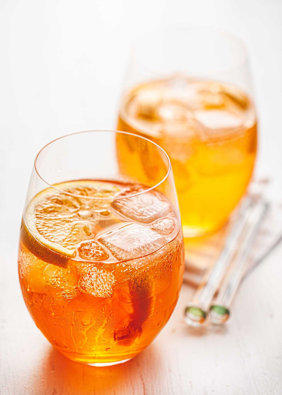 Aperol spritz in a wine glass with ice and orange slices. A second glass is behind it with stir sticks and cocktail napkins.