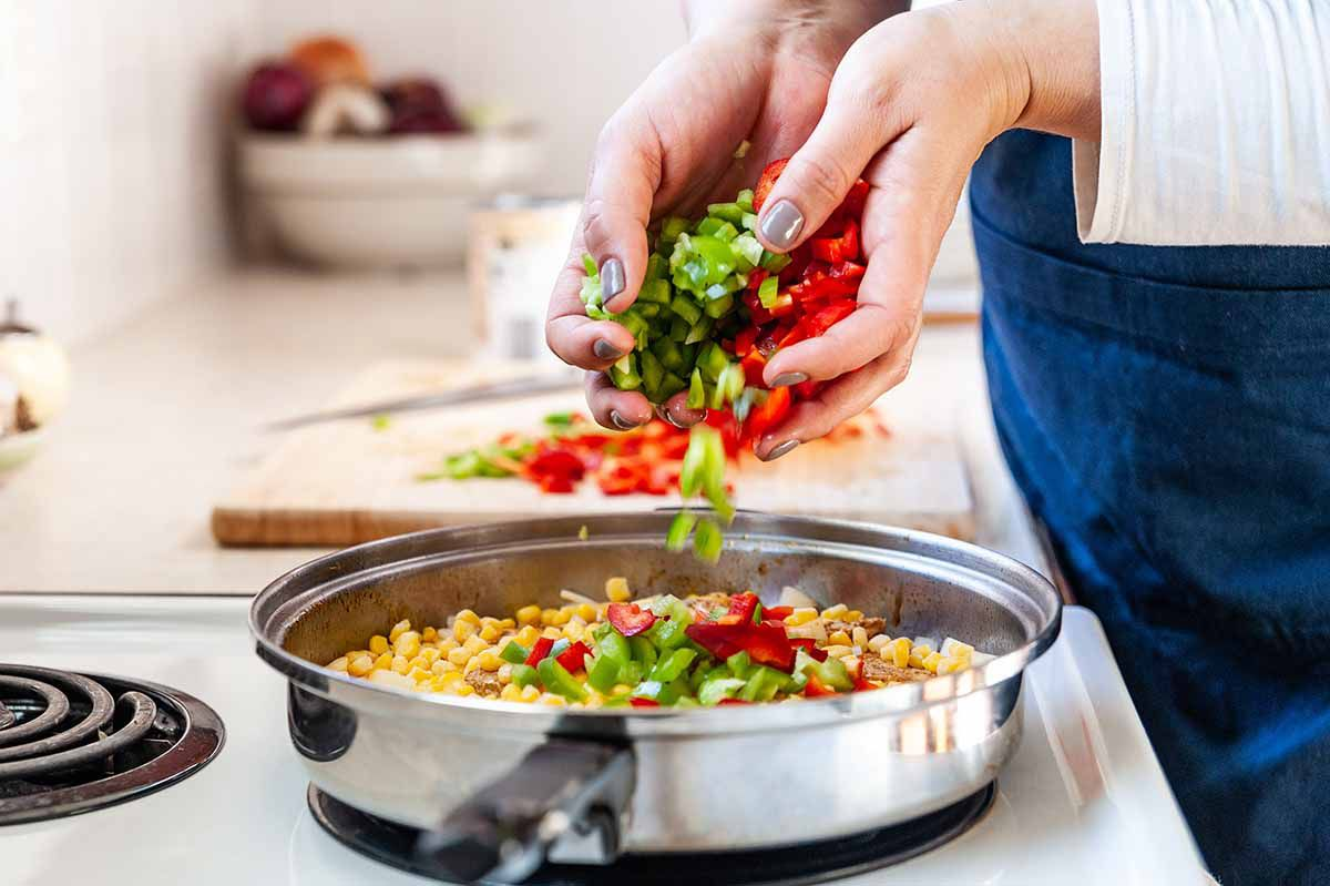 Chicken Recipe in Skillet with Smoked Paprika -- woman's hands adding chopped vegetables to skillet with chicken