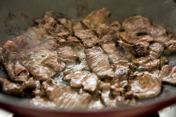 beef strips being cooked in pan