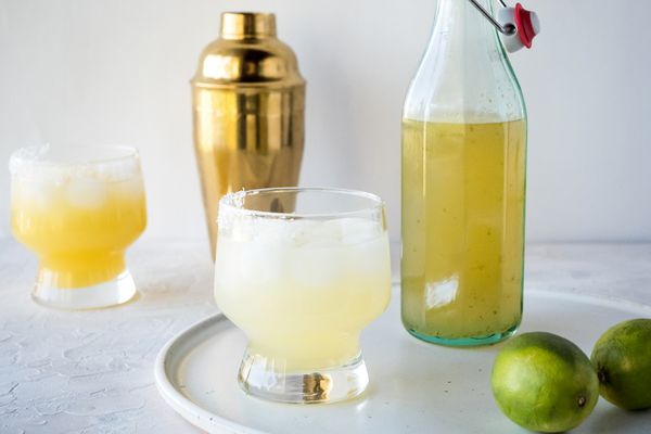 Side view of a margarita and a jar of homemade margarita mix.