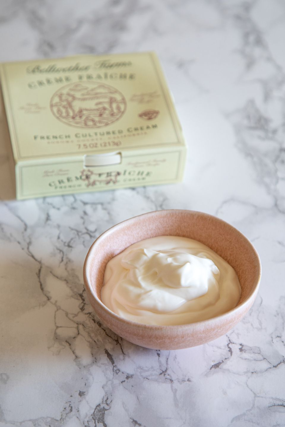 A bowl of Crème Fraîche and its packaging behind it.
