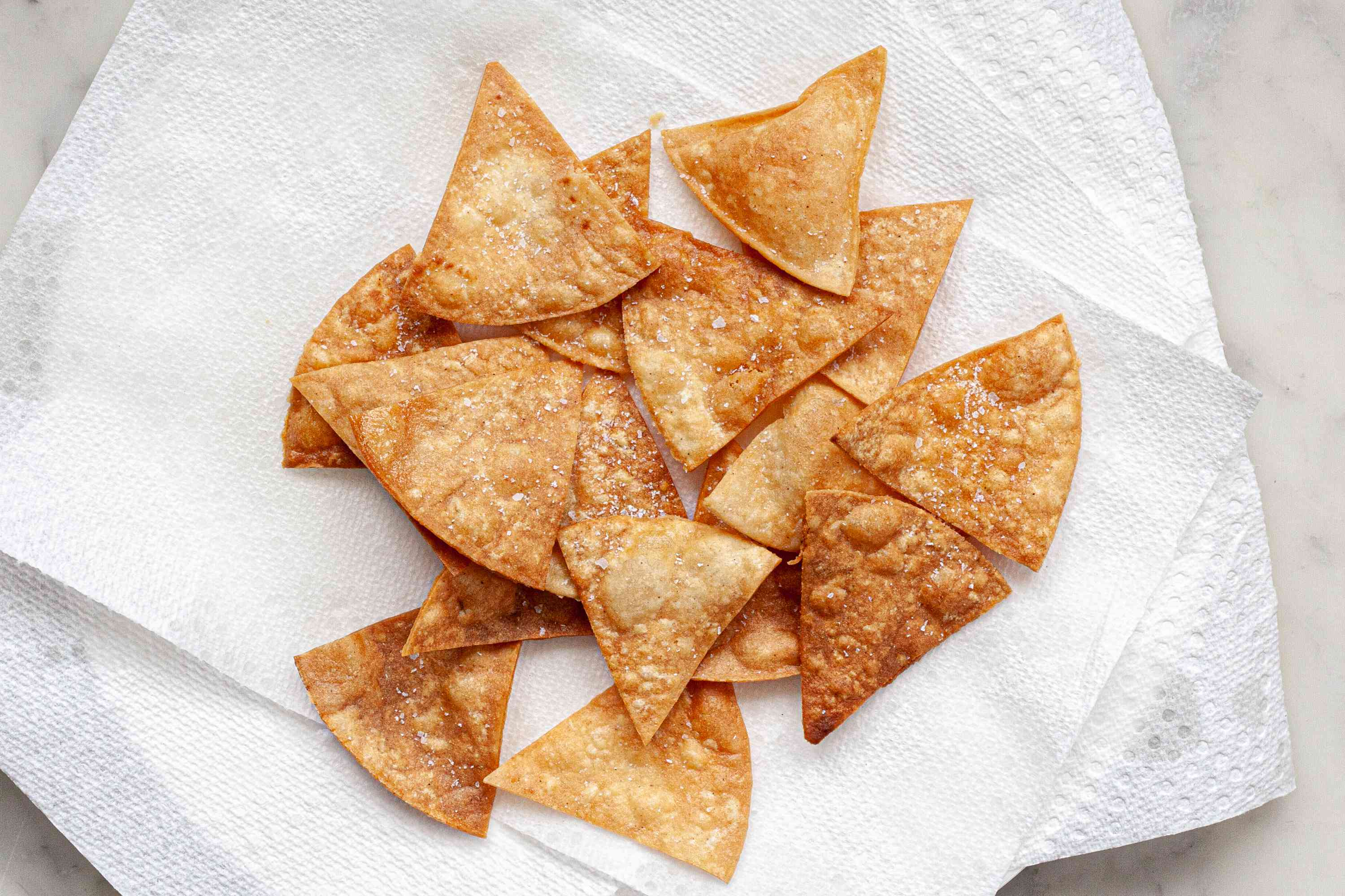 Crispy homemade tortilla chips draining on paper towels.