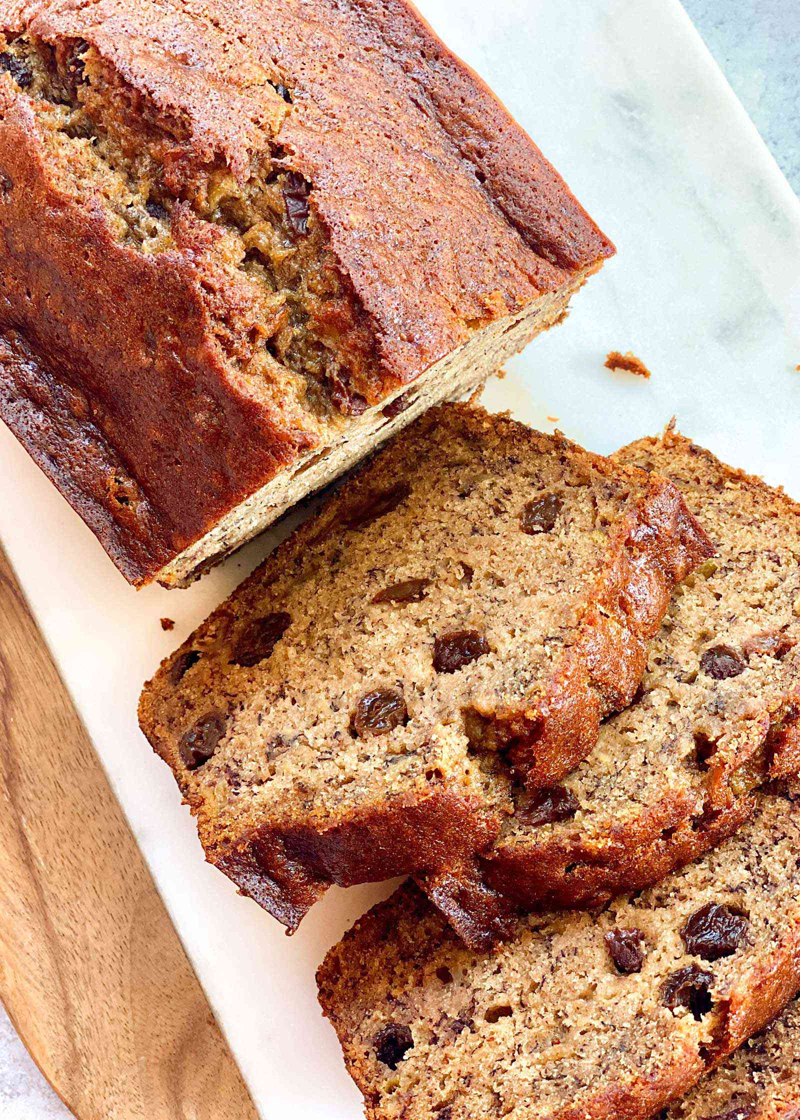 A loaf of rum raisin banana bread with four slices cut off and laying next to each other.