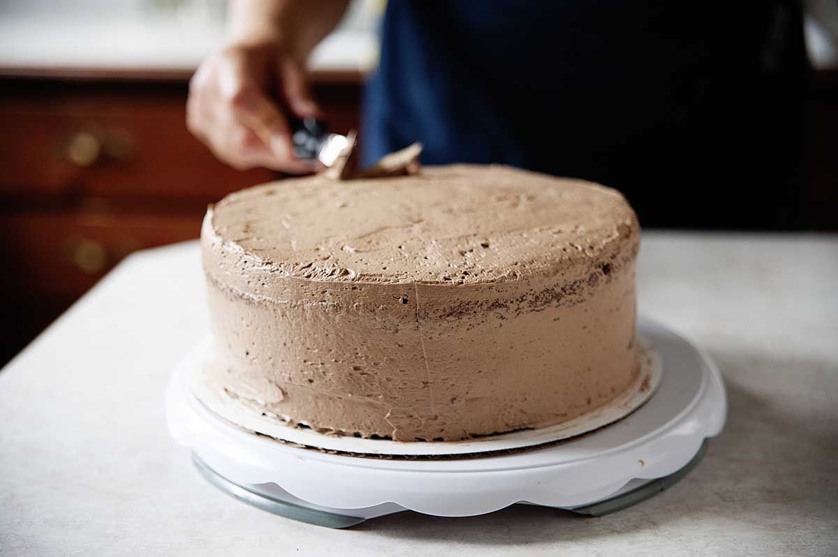 Woman using an offset spatulat to smooth creamy chocolate swiss meringue buttercream frosting on top of a chocolate layer cake