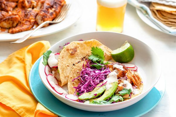 A table is set with a plate with fish tacos. Corn tortillas layered with fish, avocado, cabbage, cilantro, cheese and lime.