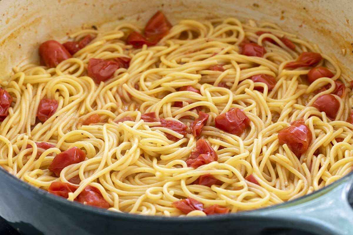 Dutch oven with easy chicken pasta skillet dinner being made. Spaghetti noodles with pasta are cooked inside the pot.
