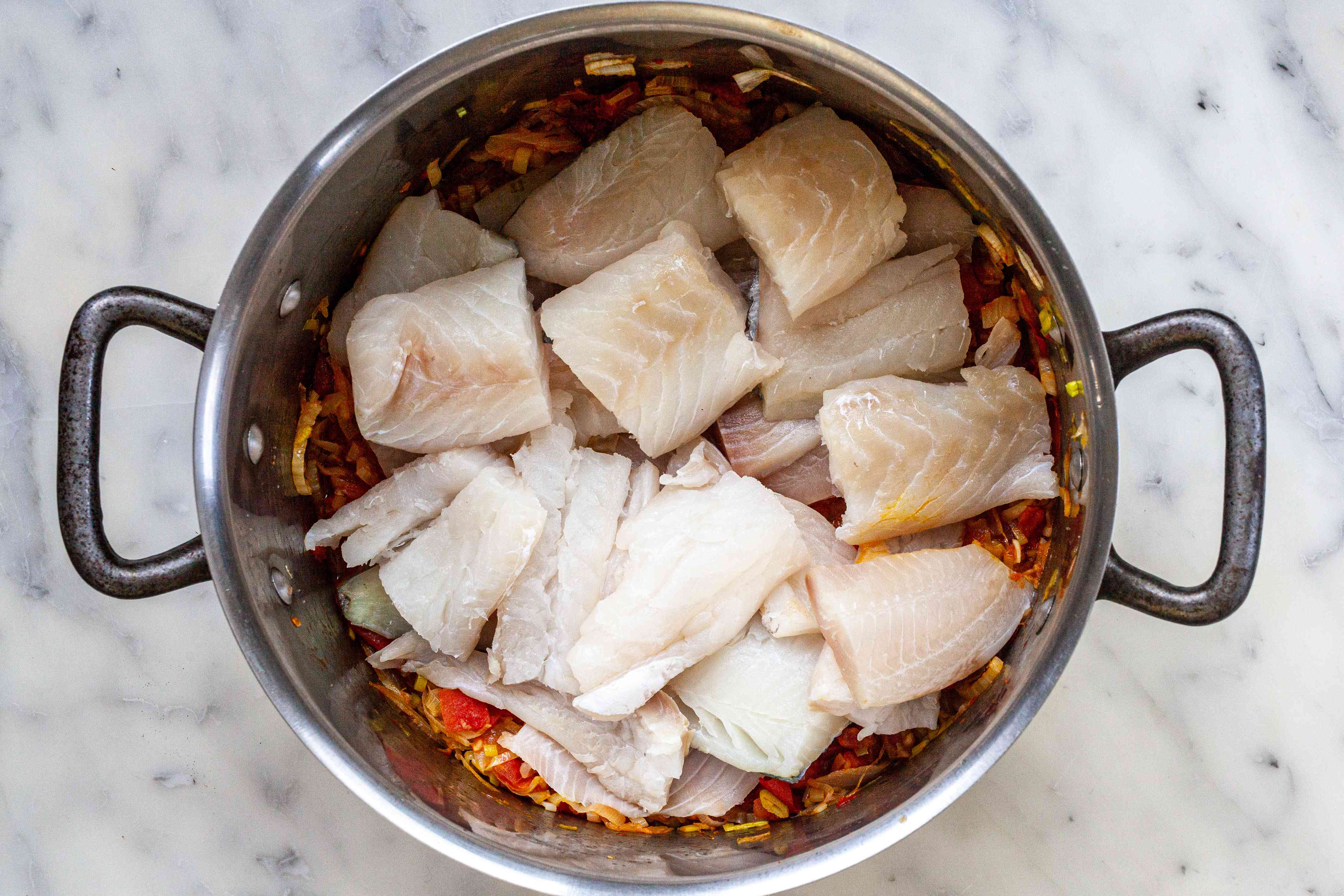Adding fish to a stock pot for a bouillabaisse recipe.