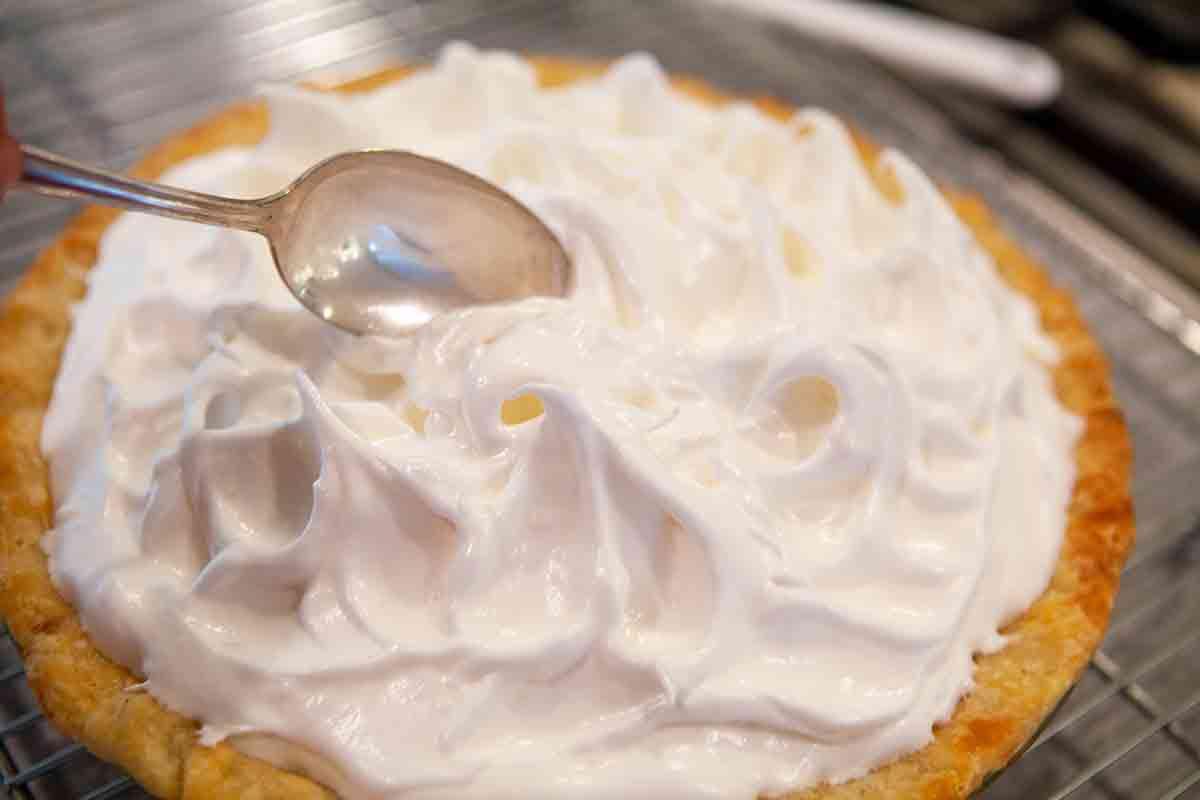 spread meringue topping over top of rhubarb filling in pie crust