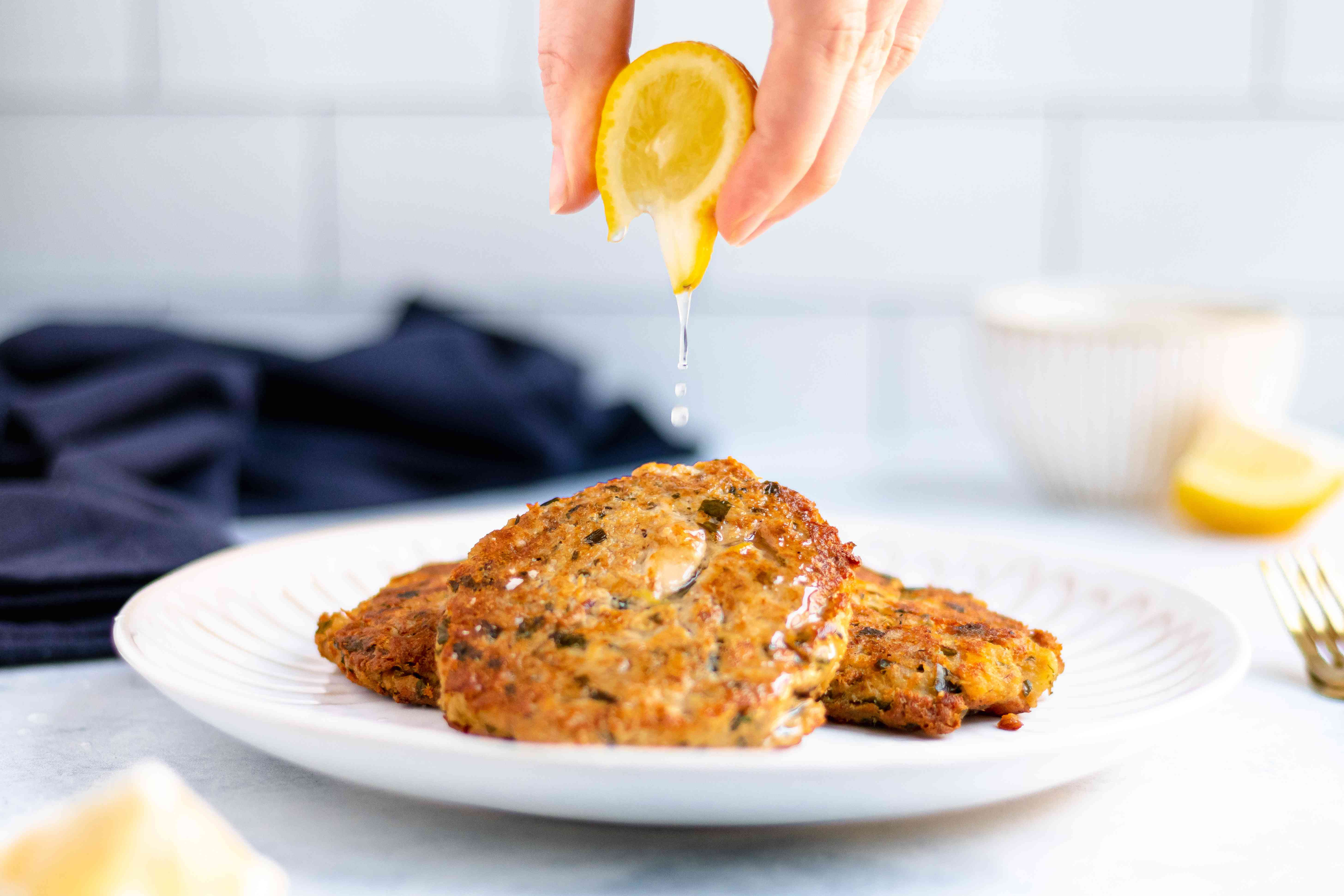 Squeezing lemon on tuna cakes.
