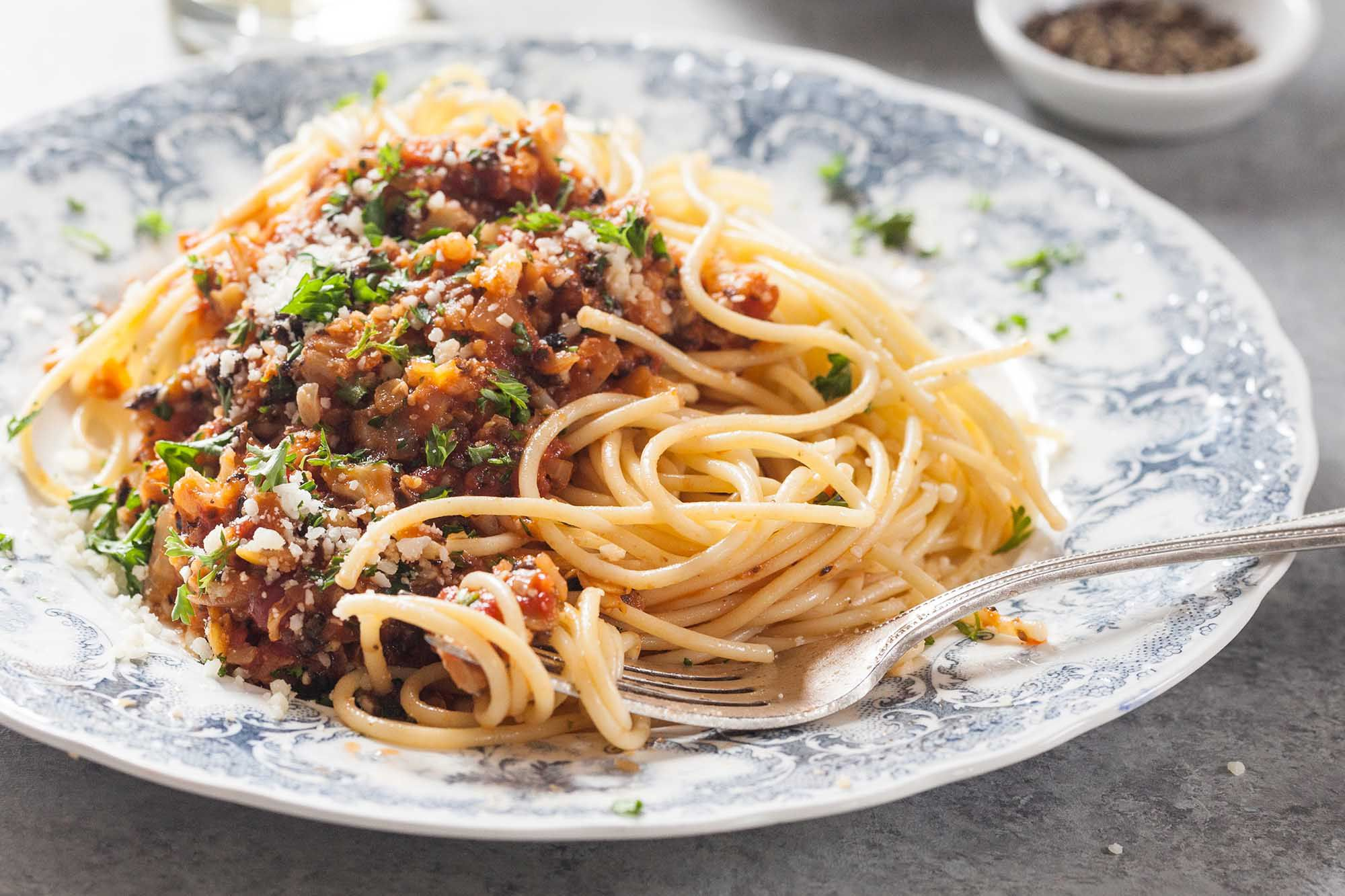 Cauliflower Bolognese on a plate with spaghetti and a fork.