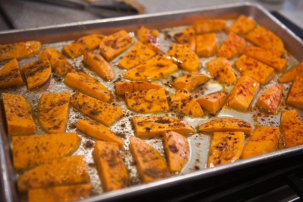 Sweet potatoes in the oven spread evenly on a sheet pan.