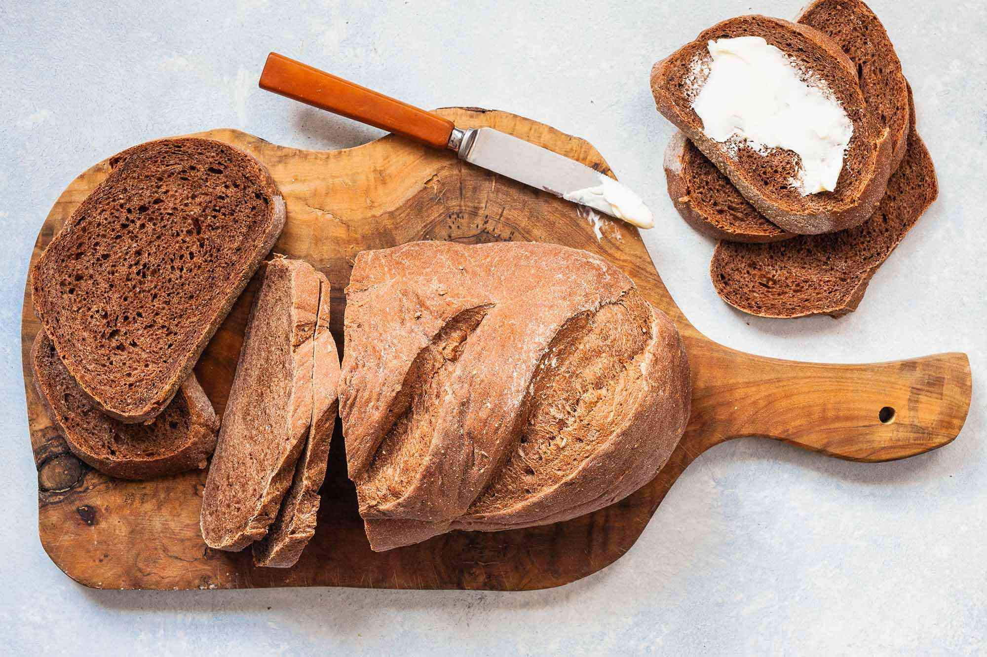 Homemade Rye Bread sliced on board with butter