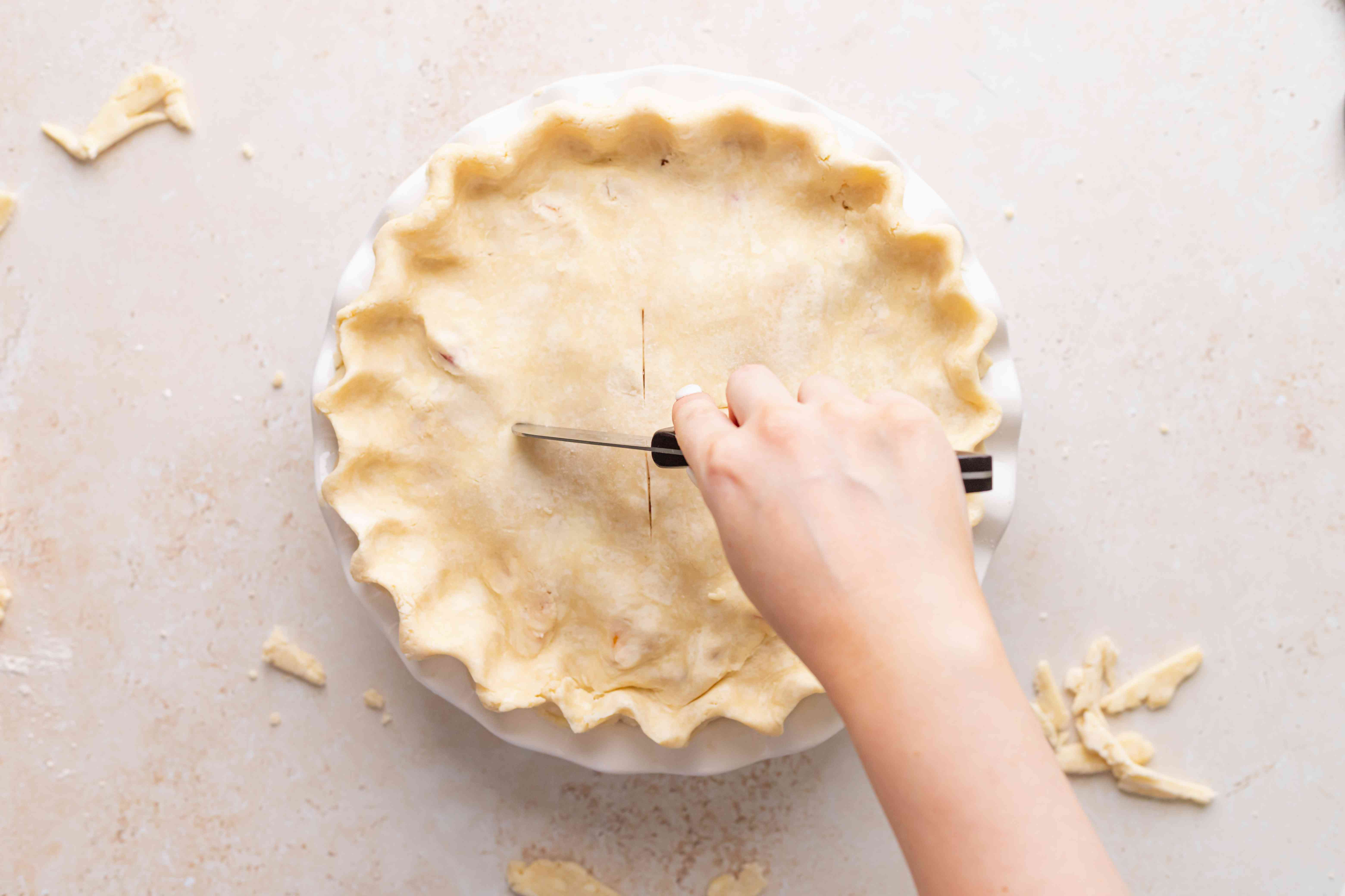 Scoring an easy peach raspberry pie before baking.