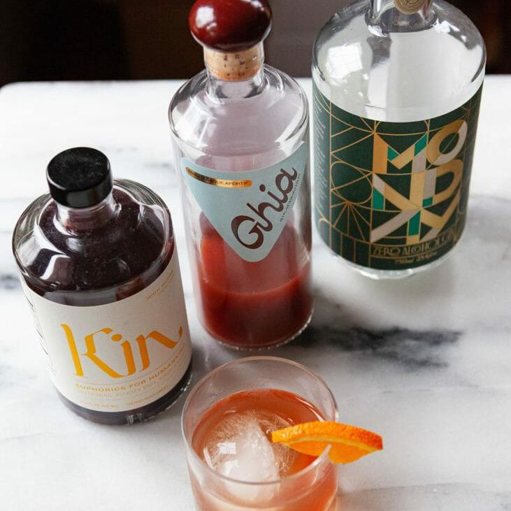 Three bottles of zero alcohol spirits and a cocktail on a table.