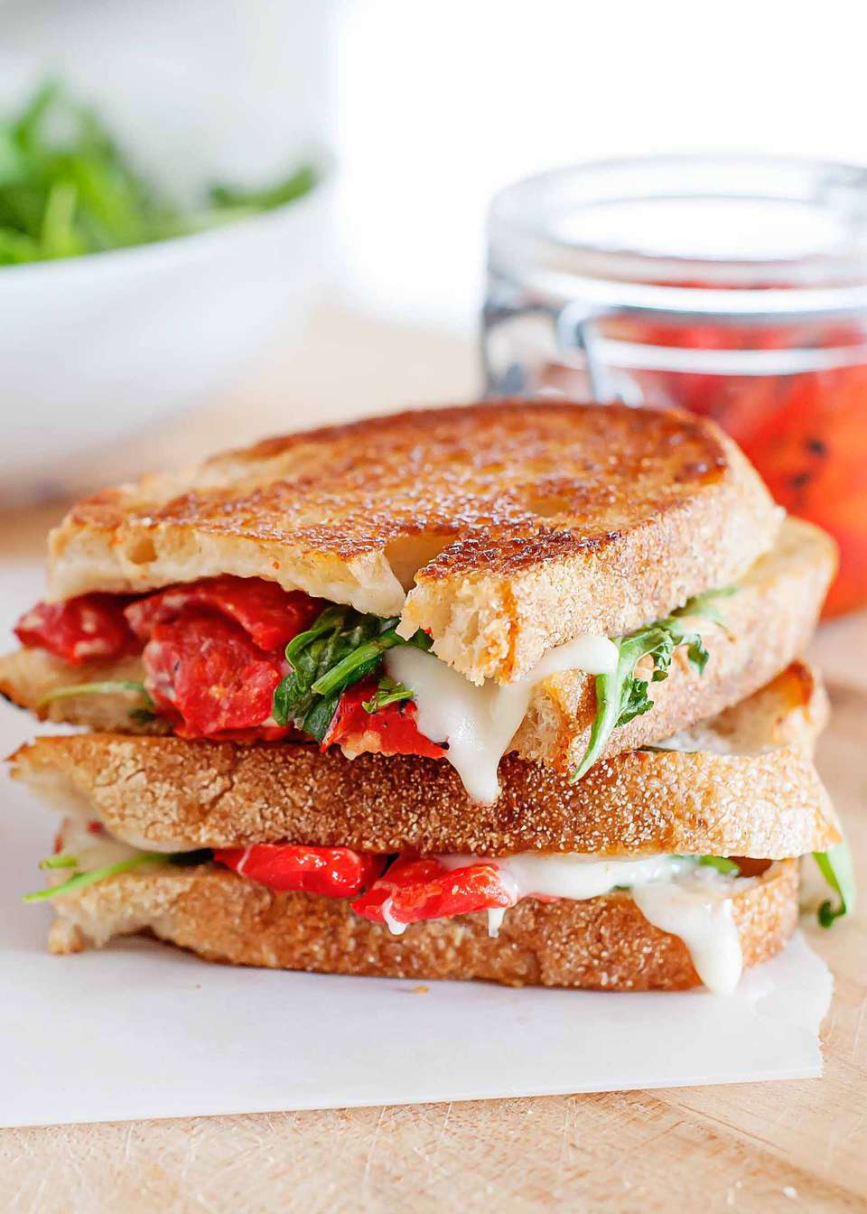 A grilled mozzarella sandwich with roasted red peppers and arugula