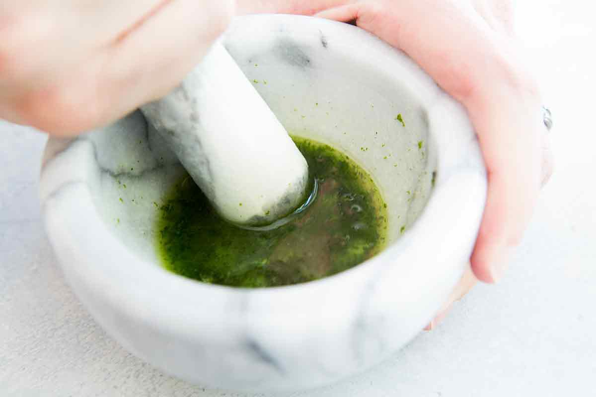 Add the remaining rum for the mojito drink to the mortar and pestle and let the mixture steep