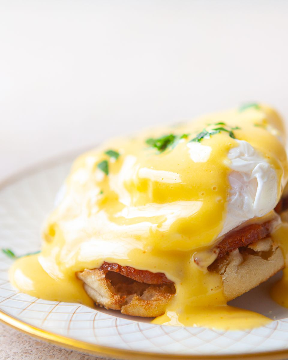 Side view of eggs benedict on a plate.