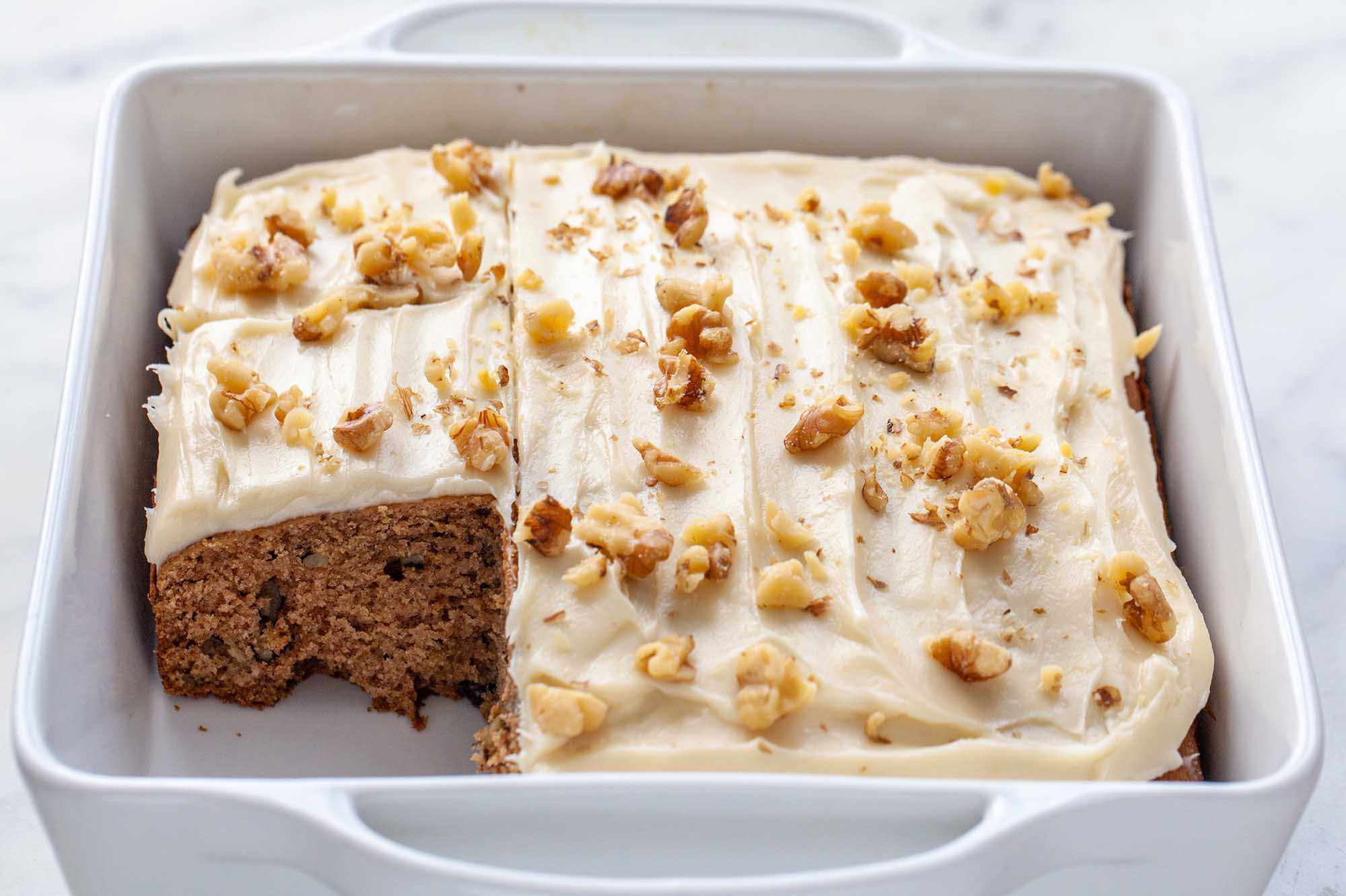 Applesauce cake, frosted and with a piece removed.
