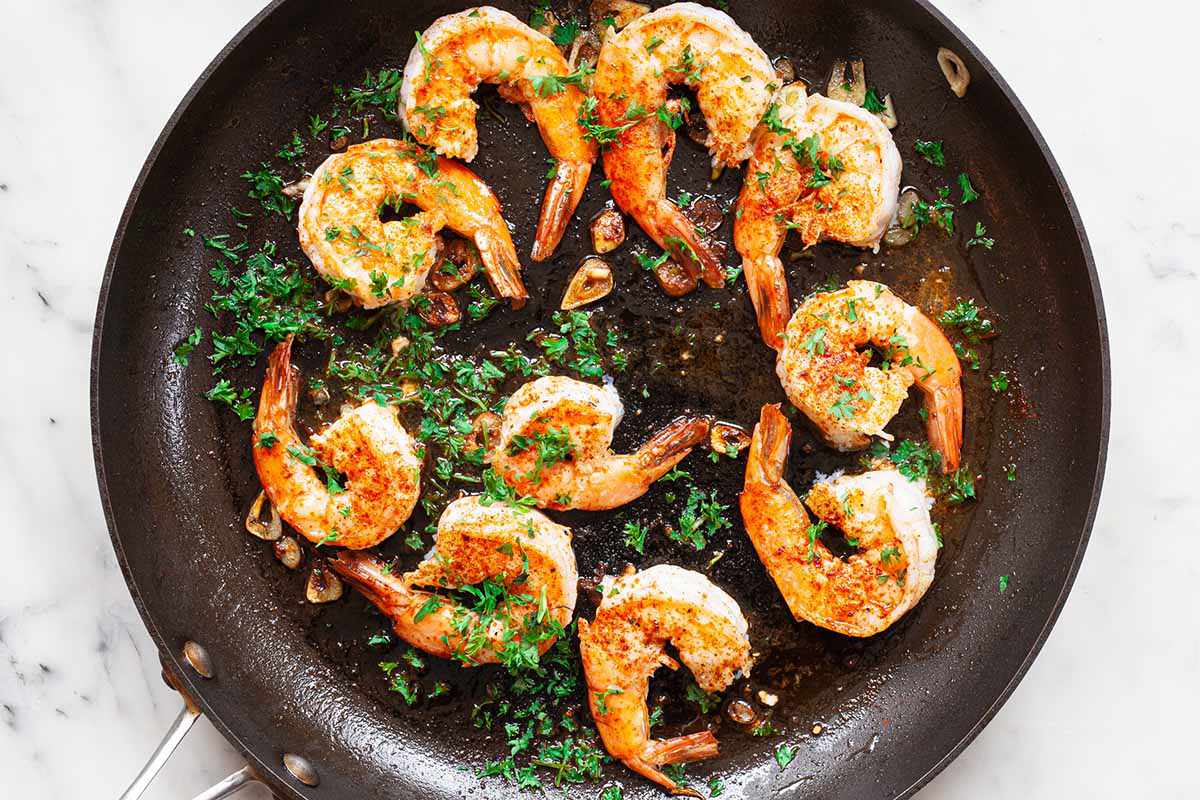 Large shrimp cooking in a non-stick skillet and covered with herbs.