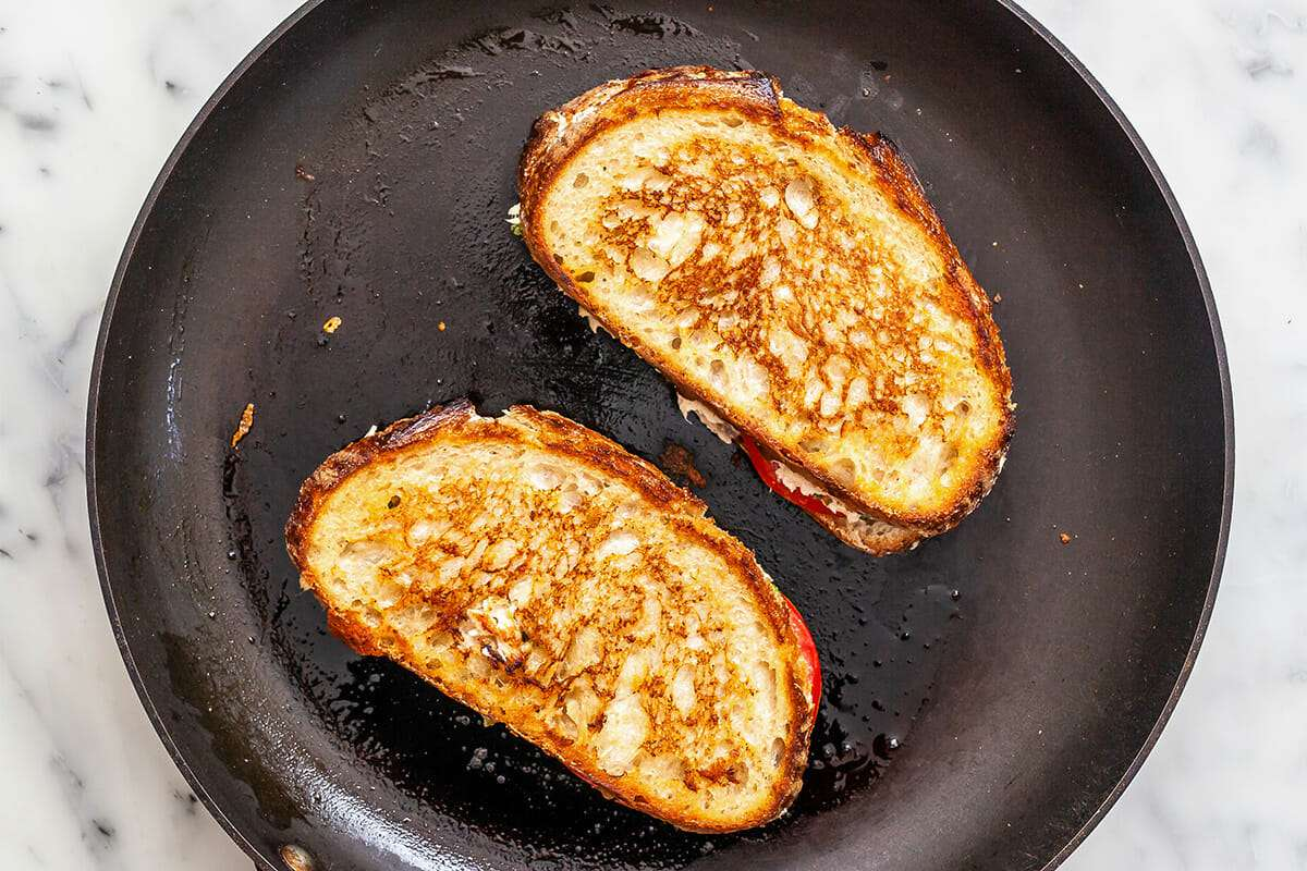 Two of the best tuna melt sandwiches toasted in a cast iron skillet.