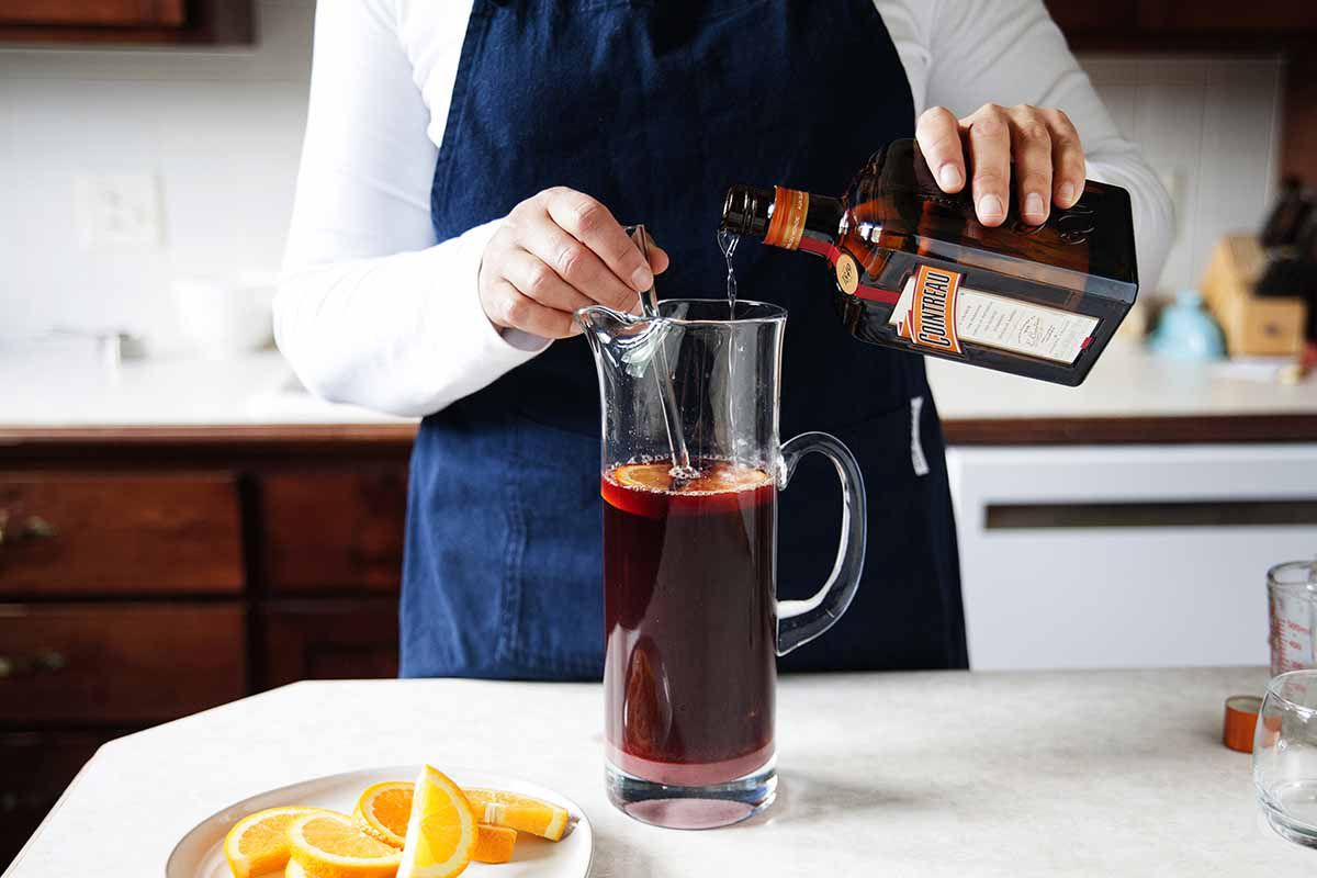 How to Make Sangria - orange slices in a pitcher of sangria on a silver tray with two poured glasses of sangria