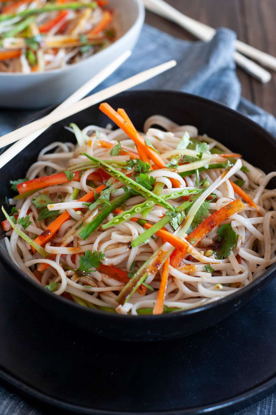 Rice noodle salad with sesame dressing in a black bowl and topped with thinly sliced vegetables.