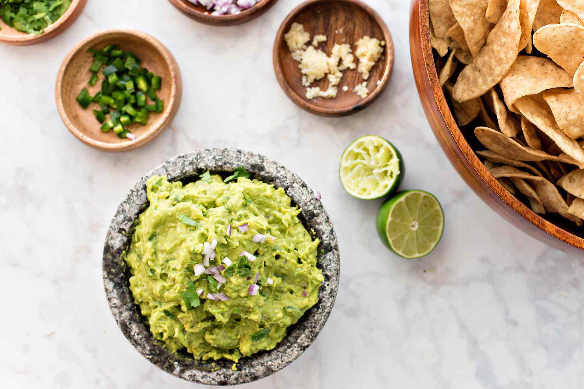 Guacamole with lime and cilantro - bowl of guacamole with smaller bowls of onion, cilantro, garlic and lime nearby and a big bowl of chips