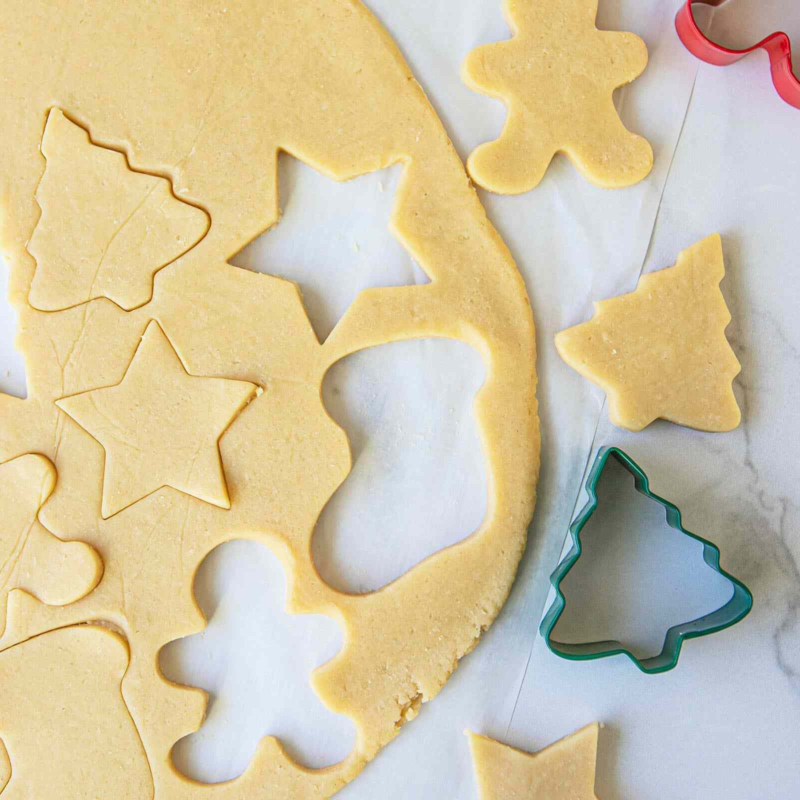 holiday cookies being cut out using a cookie cutter