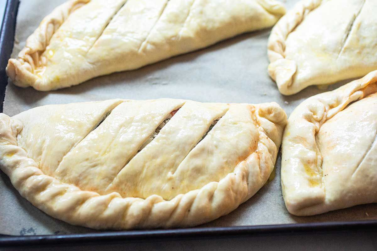 Calzones on a baking sheet with slits in the top.