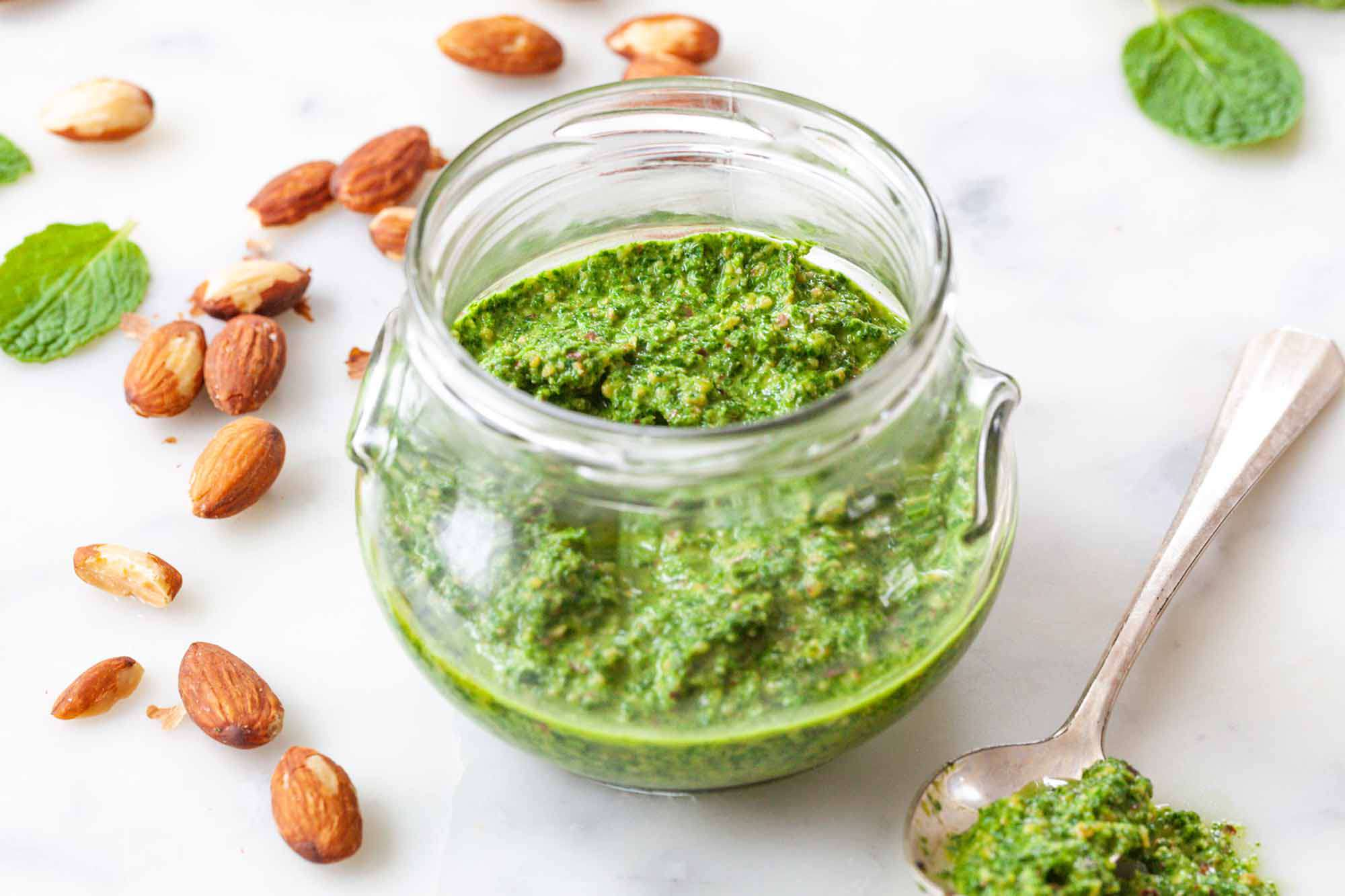 Mint Pesto Sauce - jar of mint pesto on white counter with almonds scattered about and a spoonful of pesto sitting next to the jar