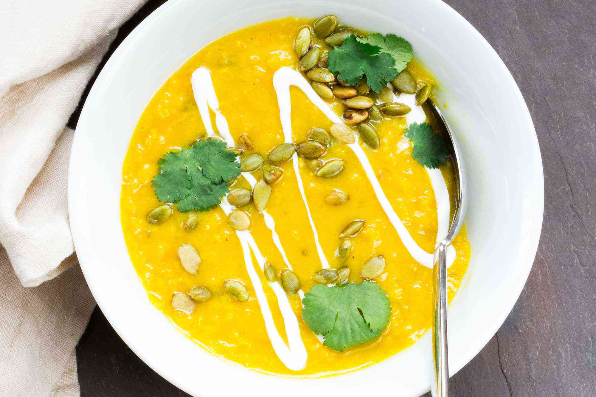 Vibrant yellow split pea soup in a white bowl with cilantro, pumpkin seeds and a drizzle of yogurt