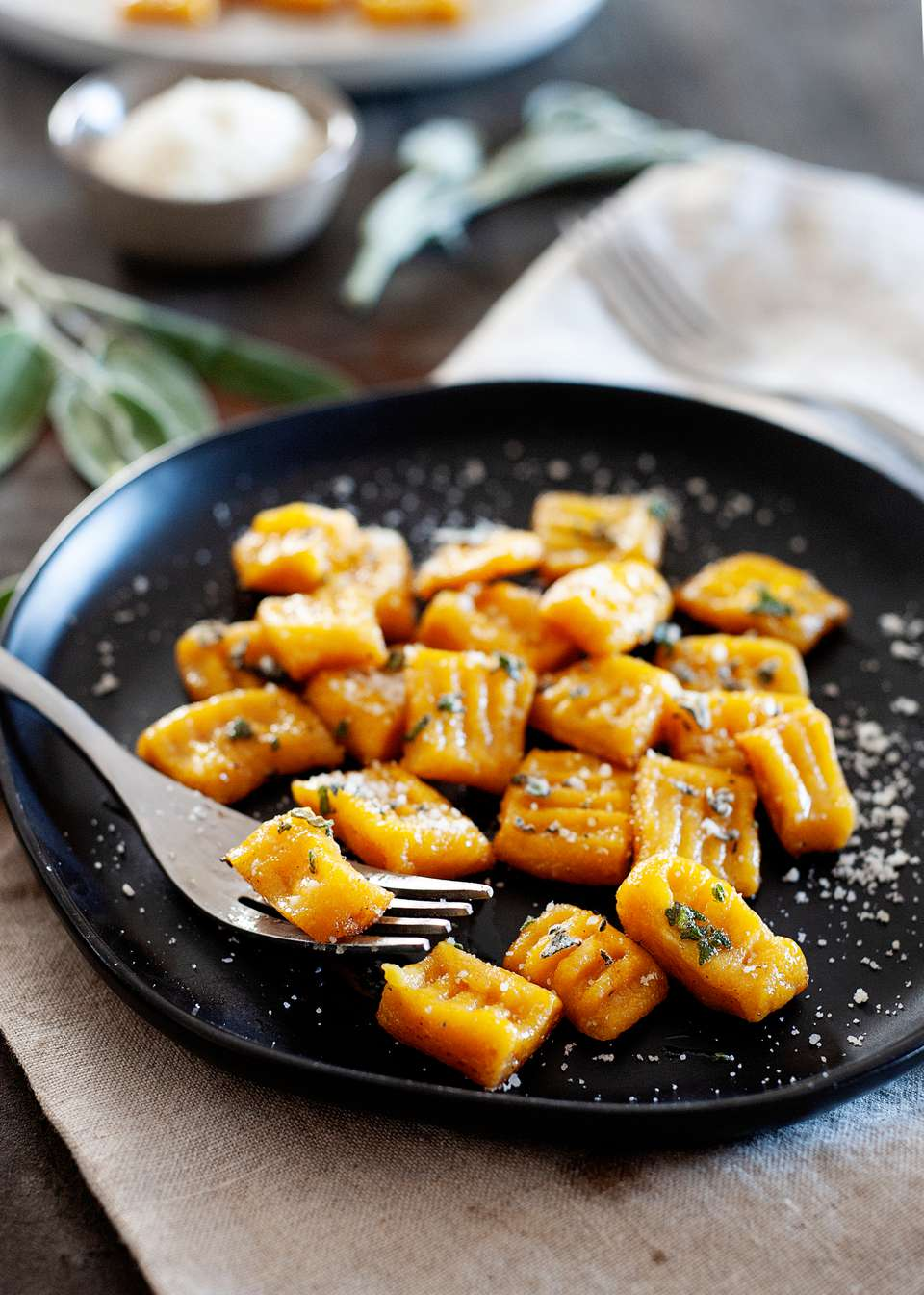 A plate of pumpkin gnocchi with a fork lifting some off the plate.