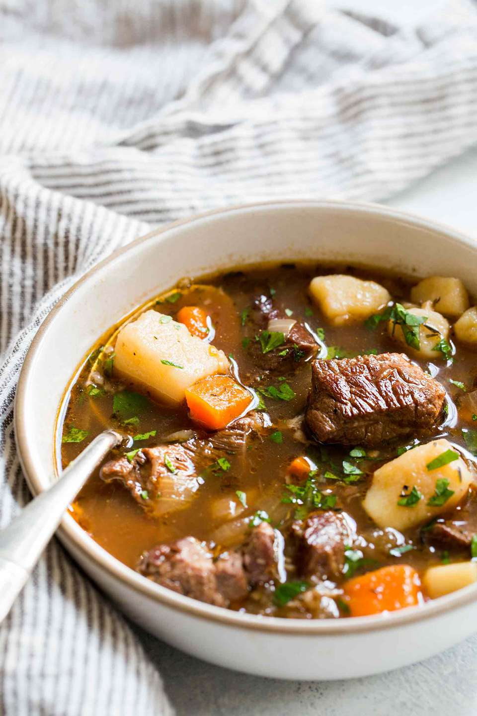 Beef stew recipe made with chuck roast, carrots, and potatoes served in a bowl with a spoon