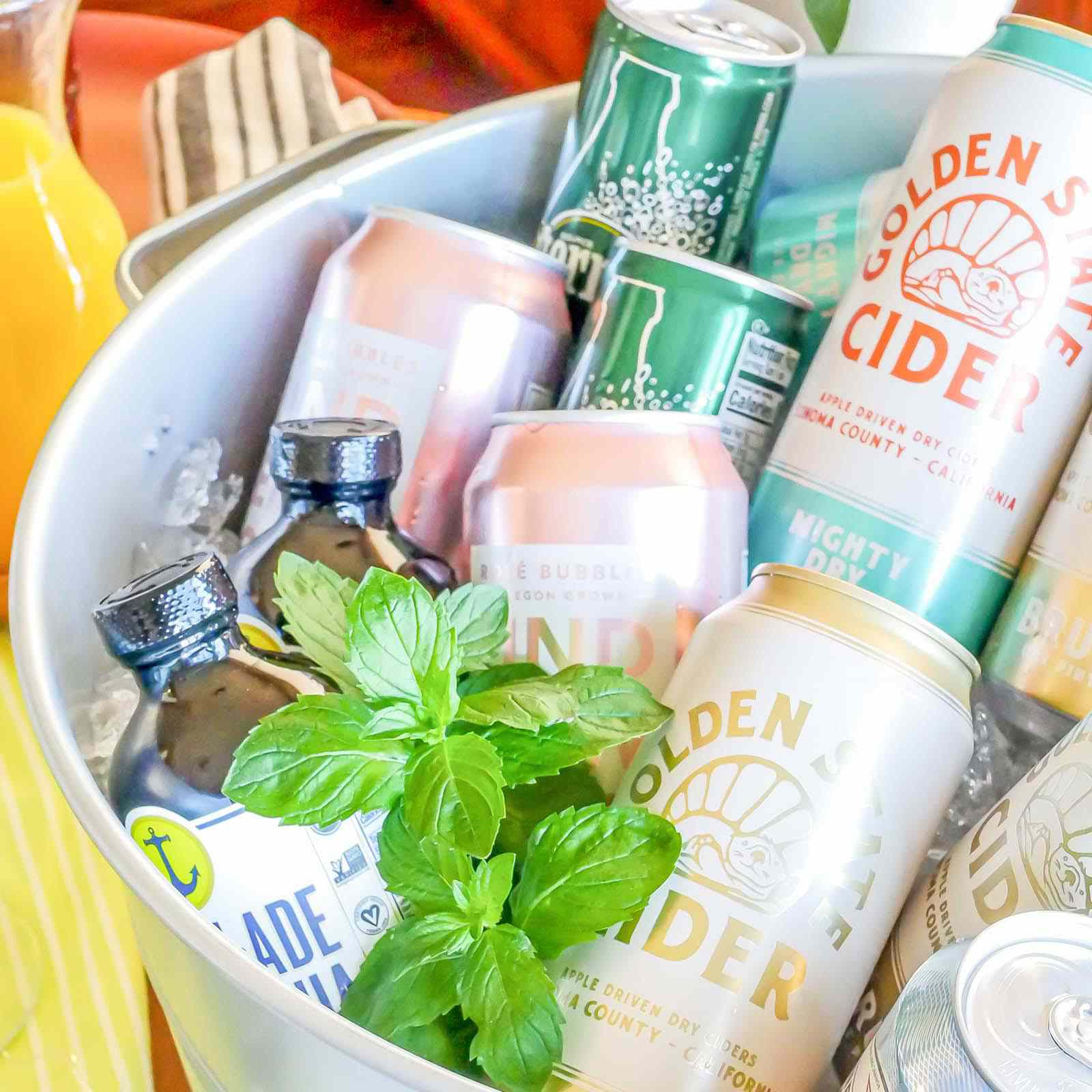 A metal tub with chilled cans of alcohol for a Mimosa Bar for Any Occasion.