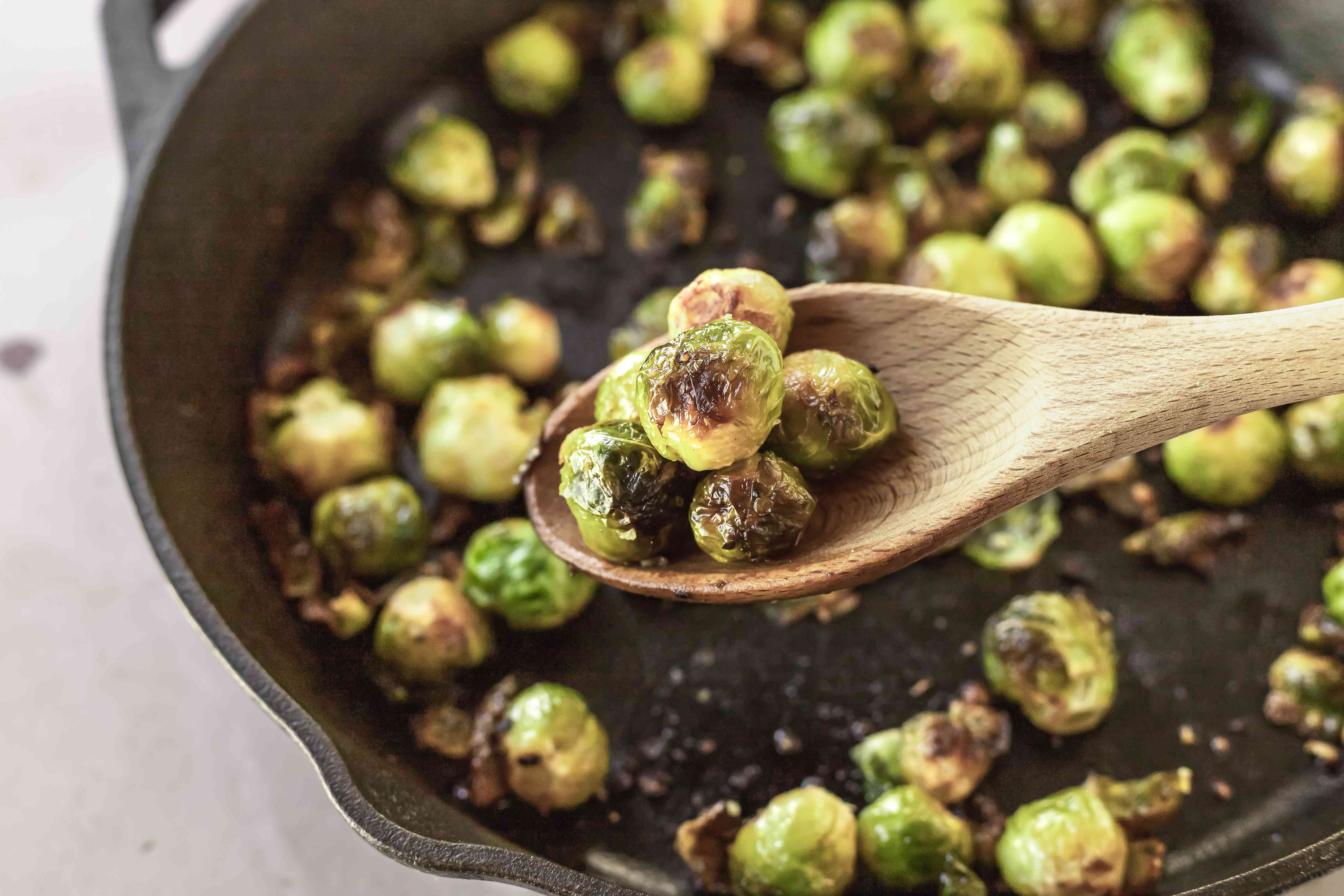 A wooden spoon scooping up roasted brussel sprouts in a cast iron pan.