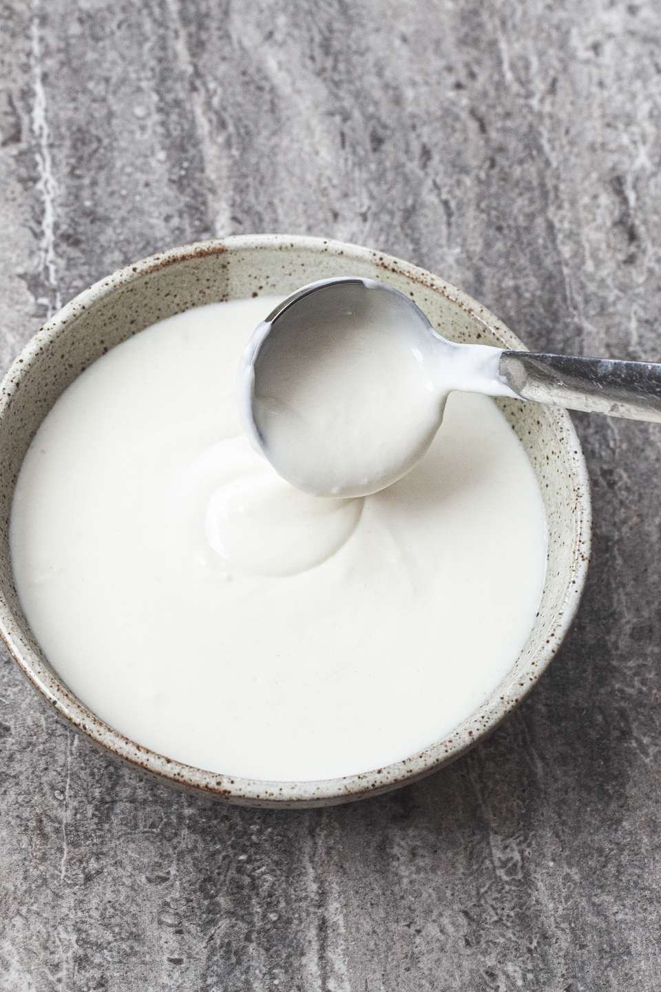 Basic béchamel sauce in a bowl with a small ladle dipping into the bowl.