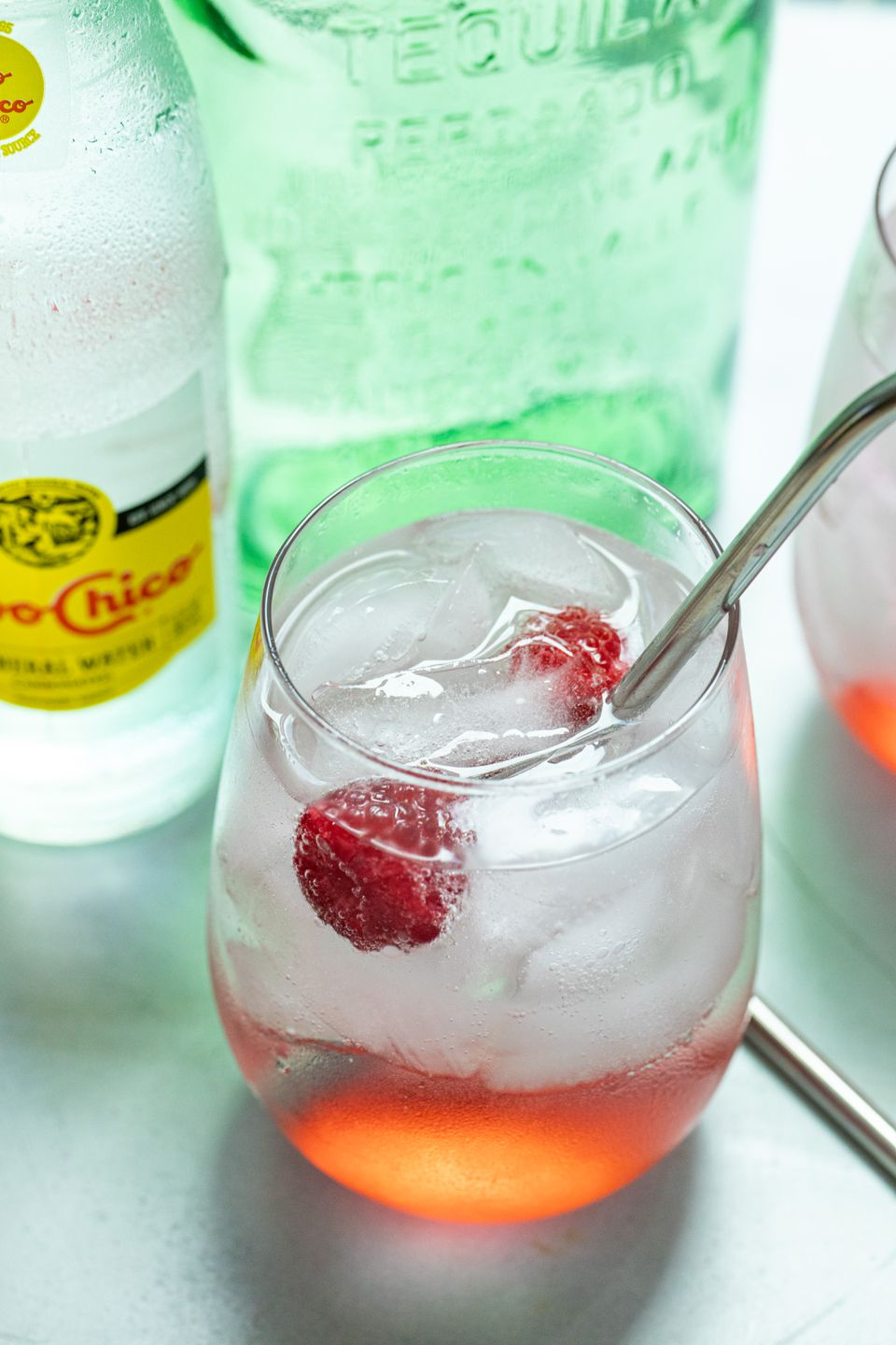 The best Texas ranch water with raspberries in a glass with a straw.