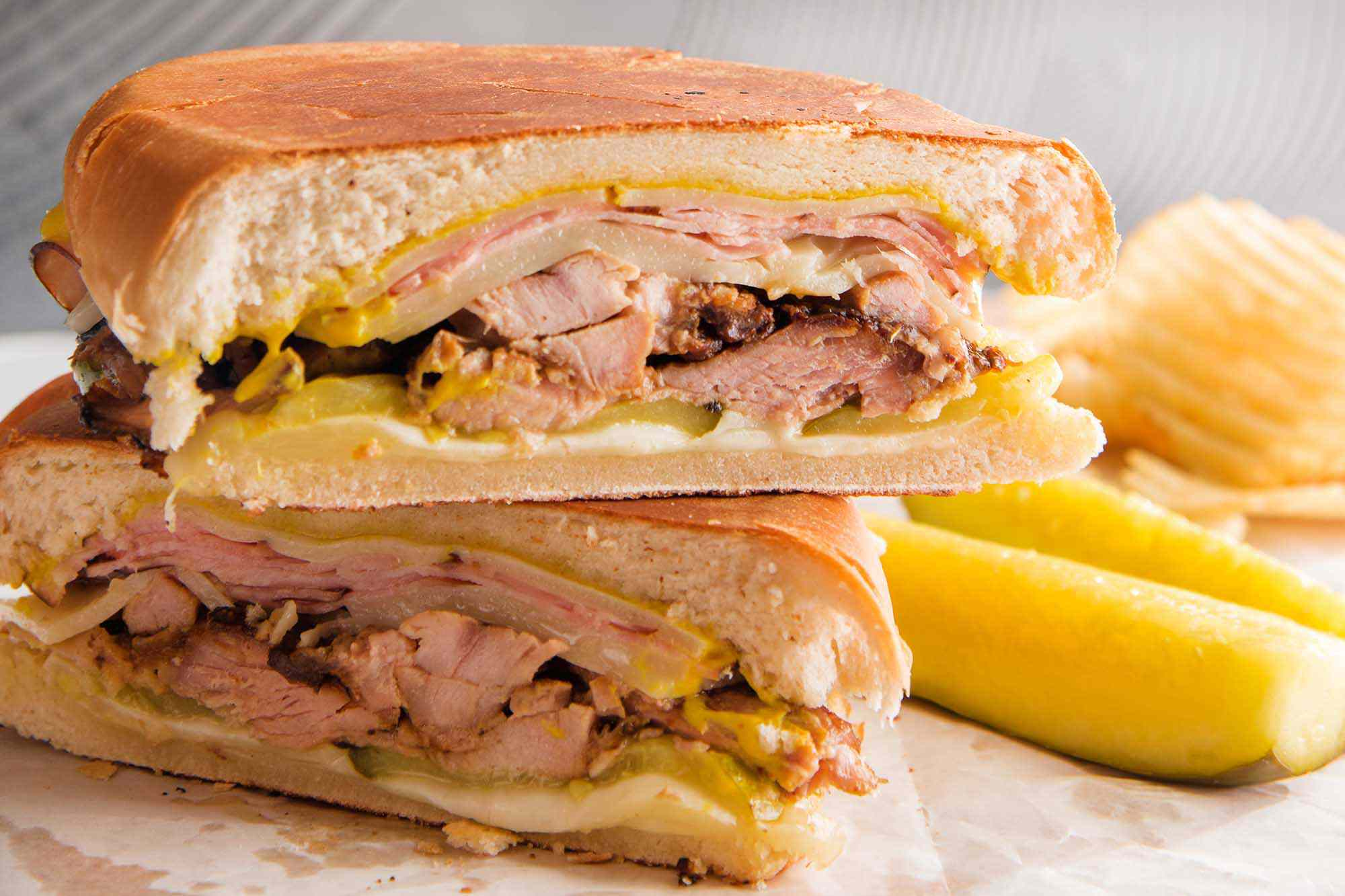 A grilled cuban sandwich is stacked on top of each other with shredded pork, mustard, cheese and pickles visible. Pickle spears and ridged potato chips are to the right of the sandwich.