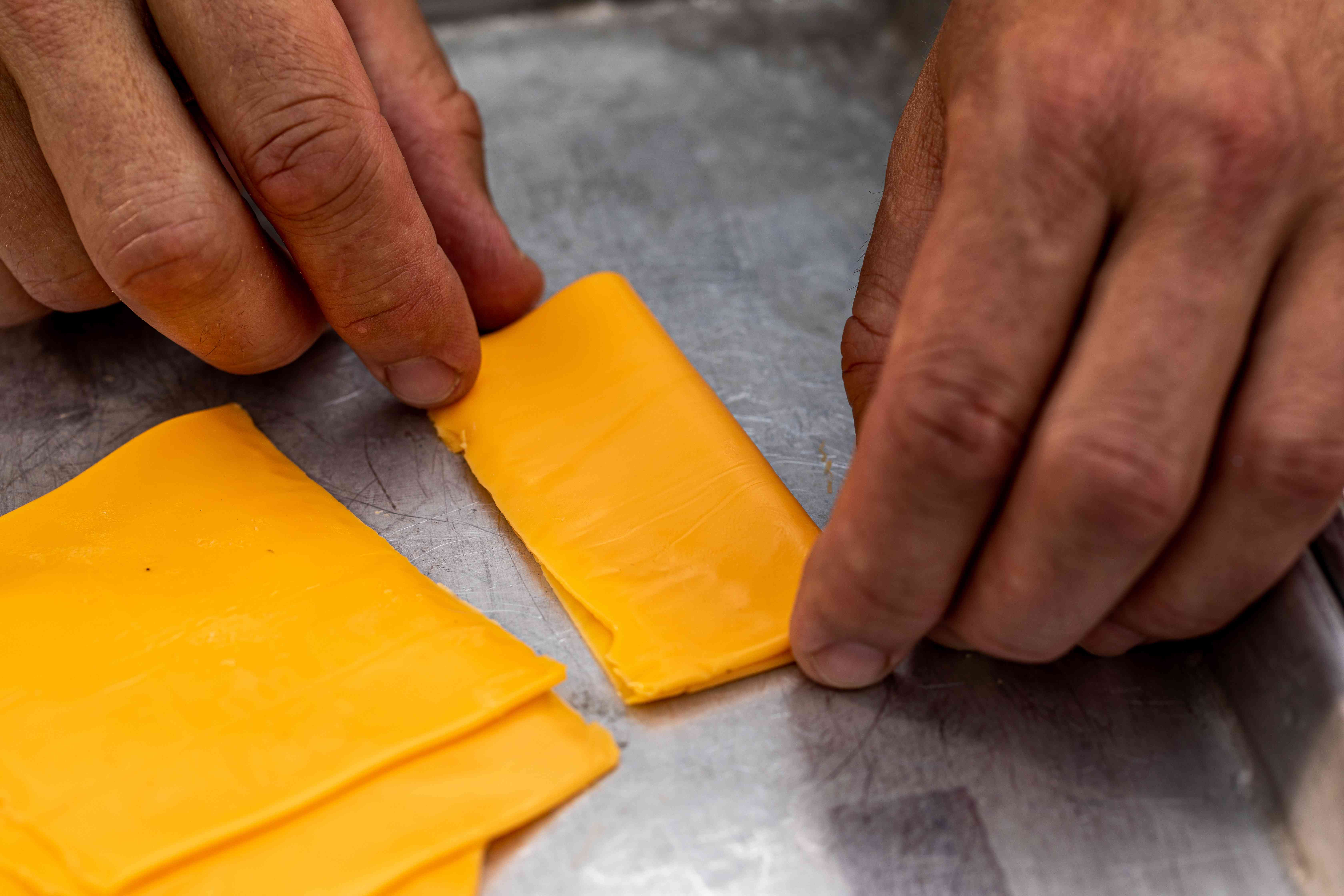 Folding sliced cheese in half to make a Juicy Lucy burger.