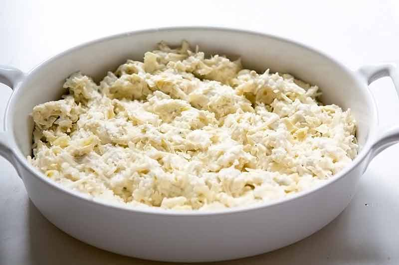 Raw Artichoke Ingredients In Large White Baking Dish