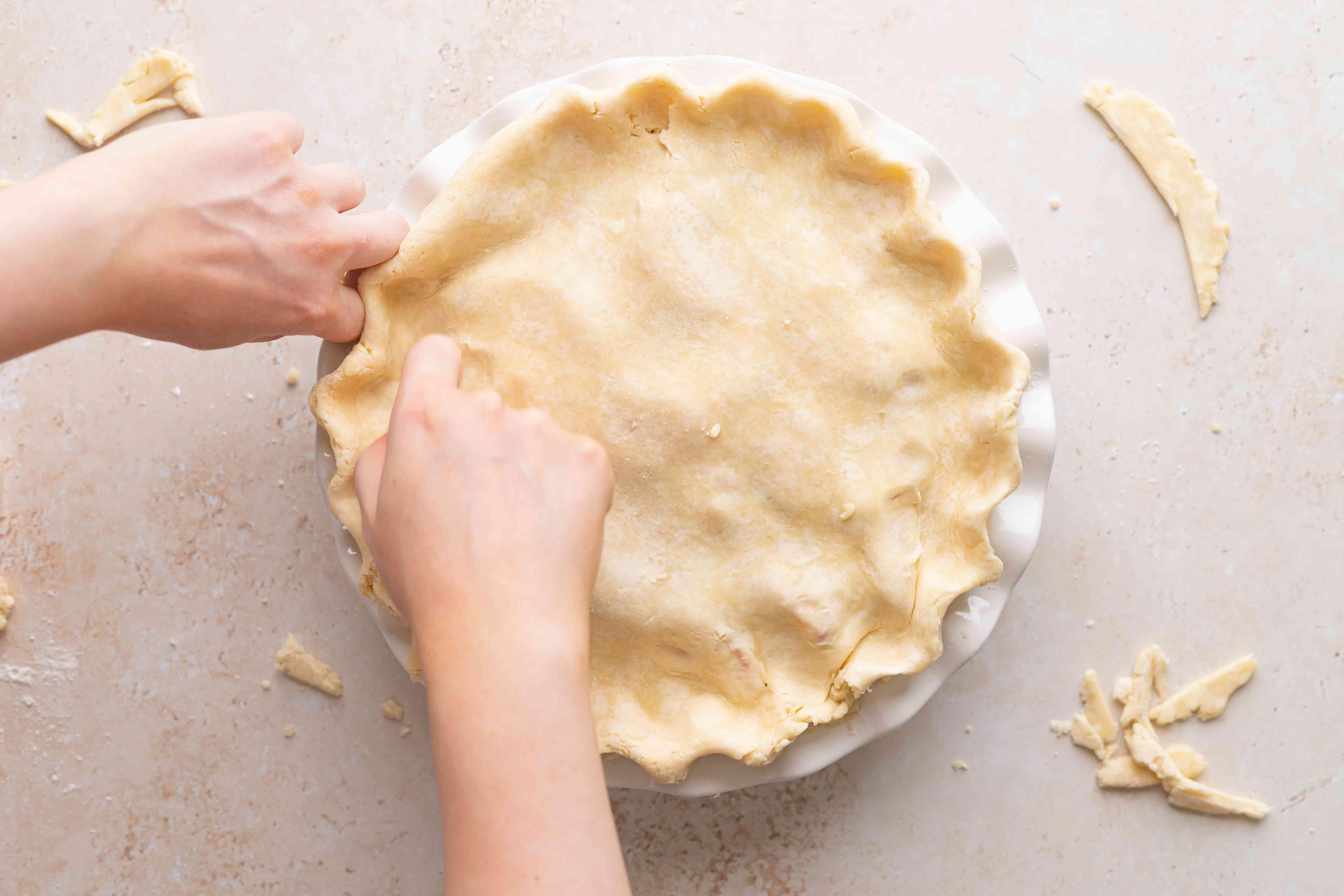 Crimping the edges of an easy peach raspberry pie.