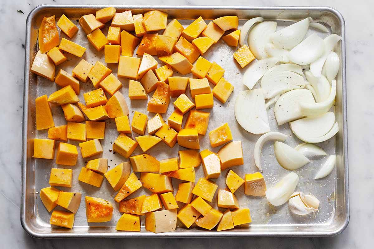 Butternut Squash and onions on a roasting pan.