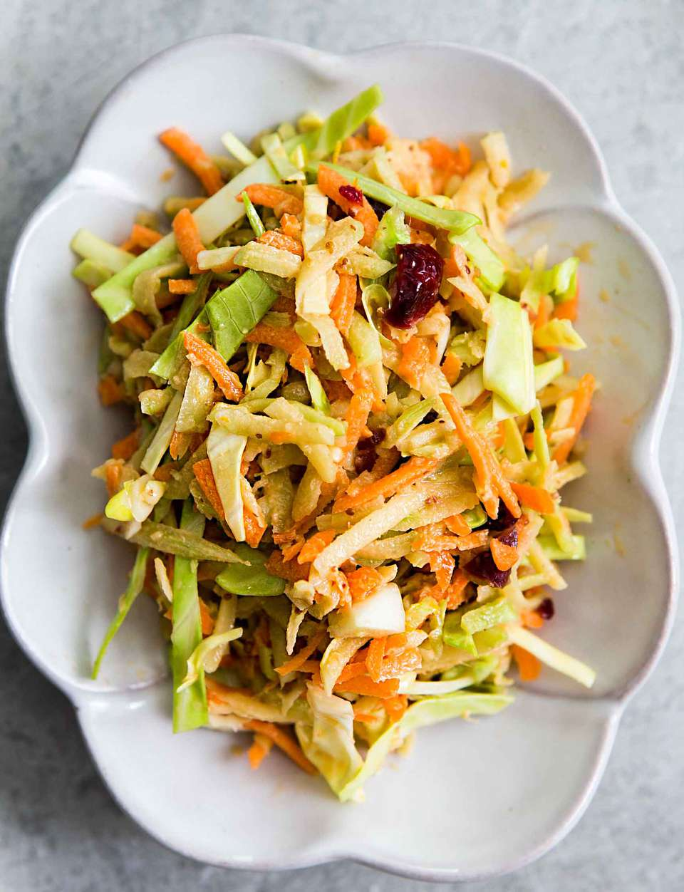 Easy Broccoli Slaw with Cranberry Orange Dressing in a white dish