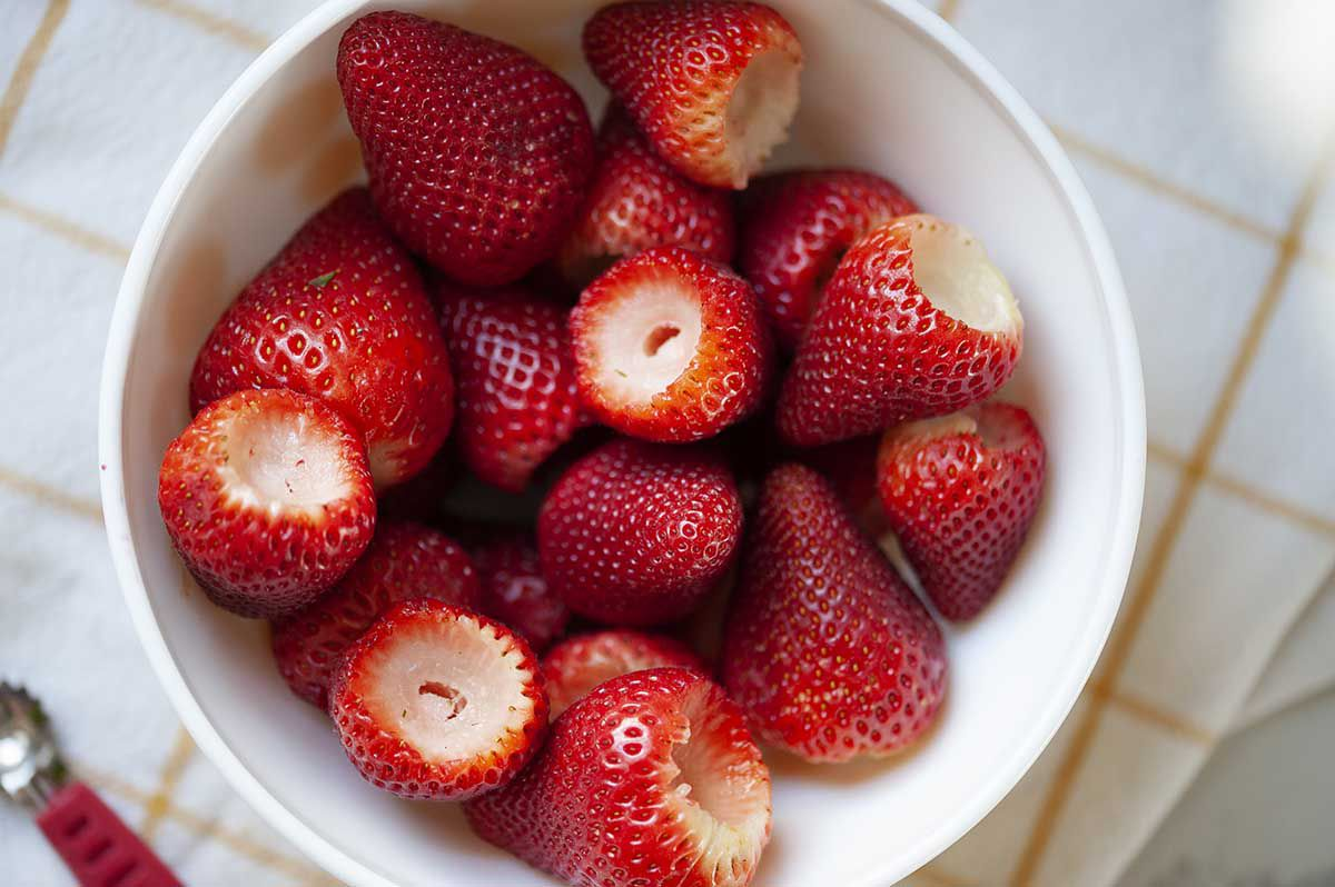 A bowl of hulled strawberries to make strawberry topping for ice cream.