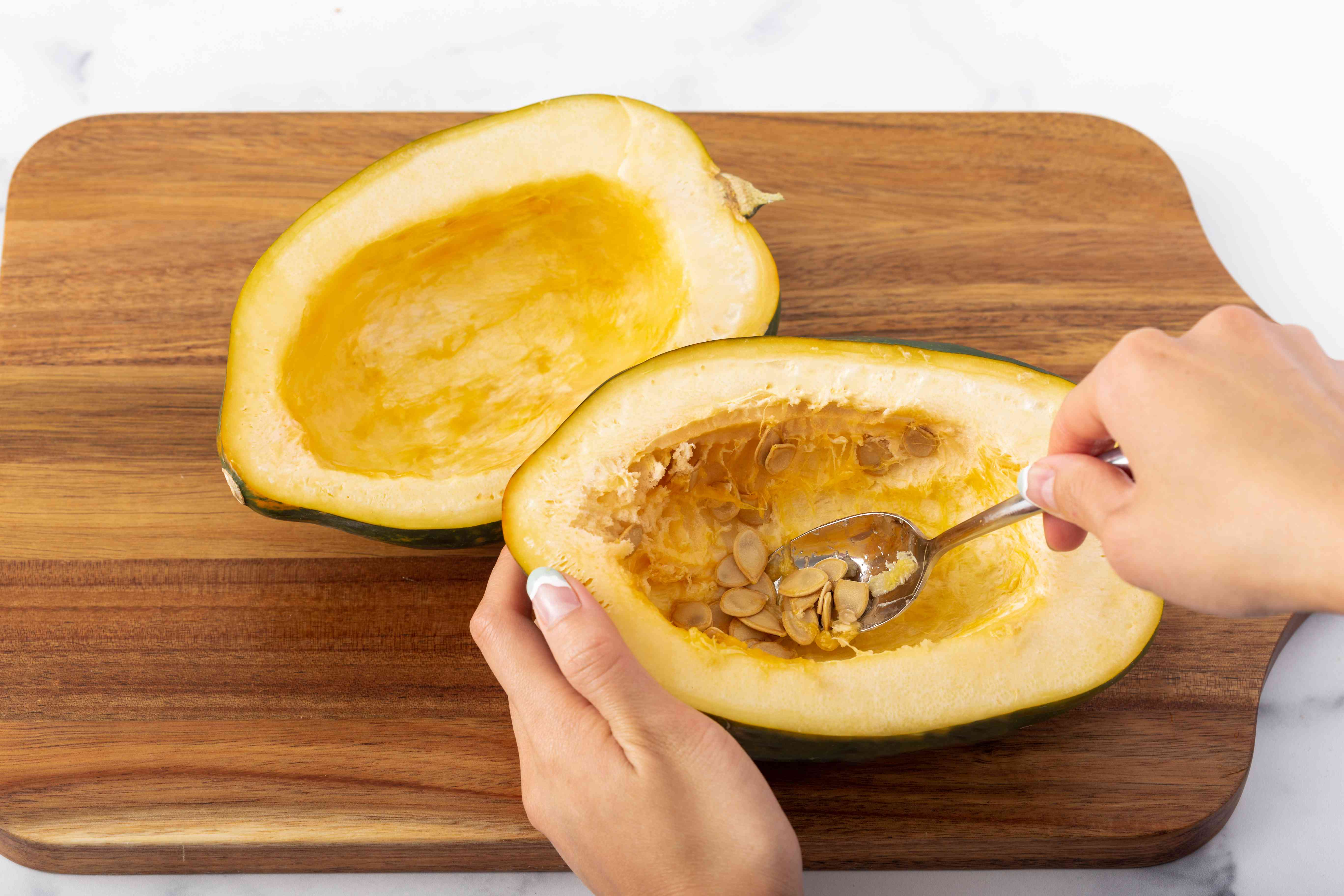 Spooning the seeds out of an acorn squash.