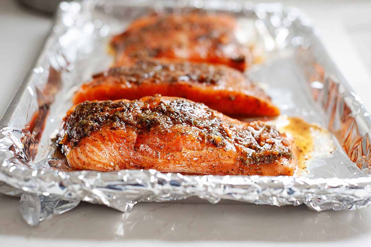 Side view of jerk salmon on a foil-lined baking tray. Seasoning coats the top of the salmon.