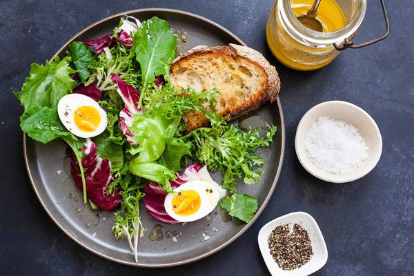 Side Salad with Eggs - - salad greens with hard boiled eggs and toast
