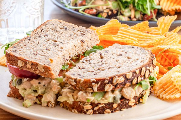 Side view of chickpea salad sandwich on a plate with chips.