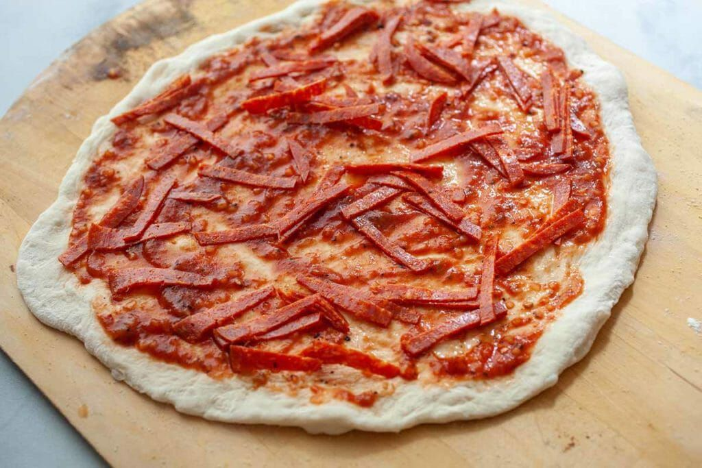 Put slices of pepperoni under the cheese layer on your homemade pepperoni pizza