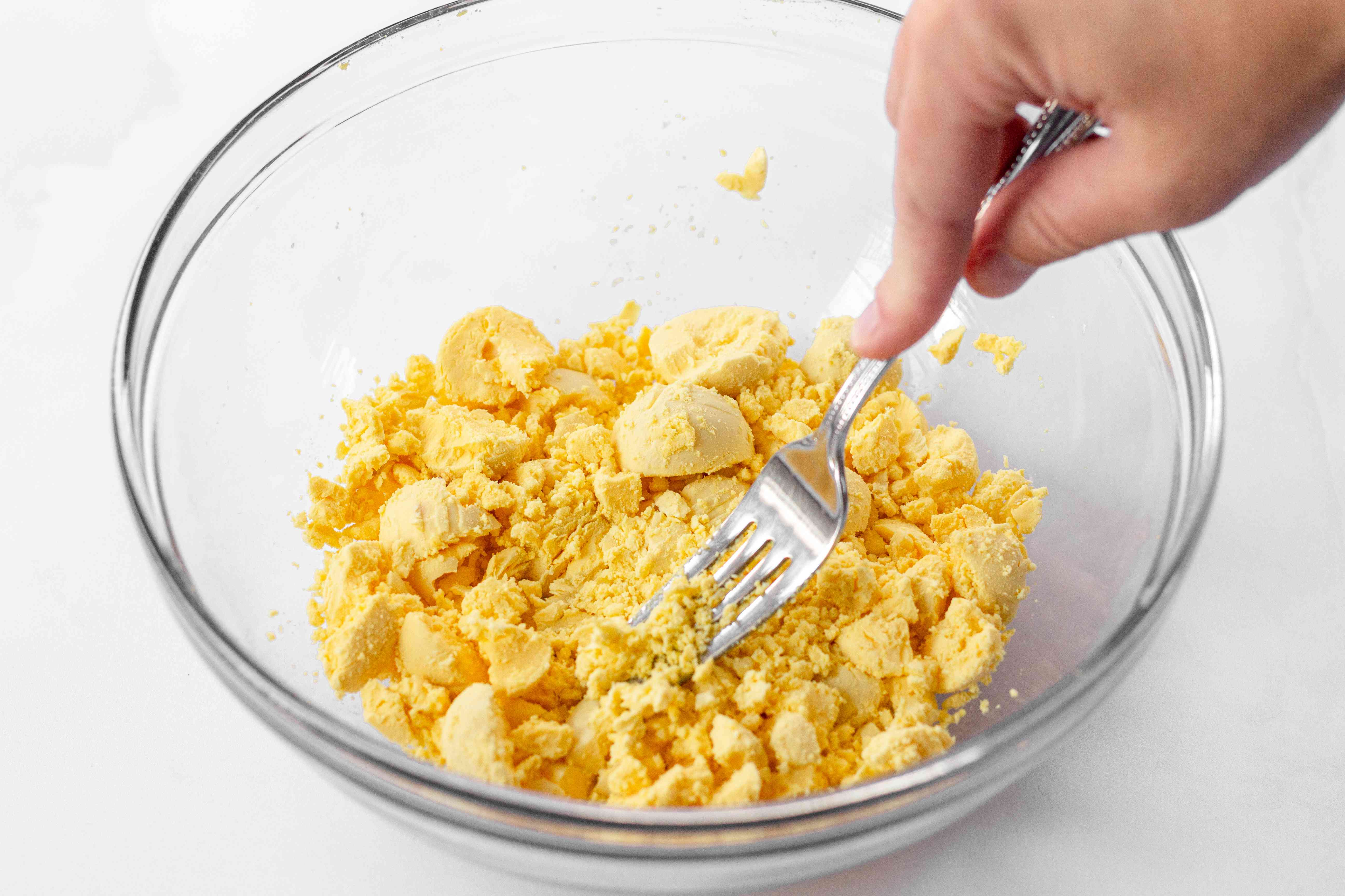 Hard boiled egg yolks mashed with a fork in a glass bowl.